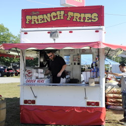 John Frake mans the Steve's French Fries booth at the Oxford County Fair earlier this month. Nearly 900,000 people are expected to visit Maine's agricultural fairs in 2015, according to the Maine Department of Agriculture, Conservation and Forestry. More than $1.5 million in premiums went to exhibitors this year. The season ends next month with the Fryeburg Fair, which runs Oct. 4-11. Gordon Chibroski/Staff Photographer