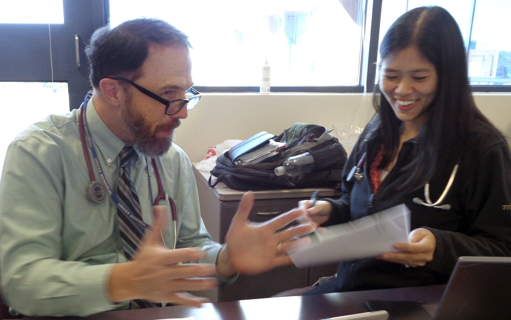 Dr. Rick Sacra reviews patient cases with Dr. Anna Chon at the Family Health Center in Worcester, Mass., where he advises doctors in training. Sacra contracted the deadly Ebola virus while delivering babies in a missionary-run hospital in Liberia a year ago.