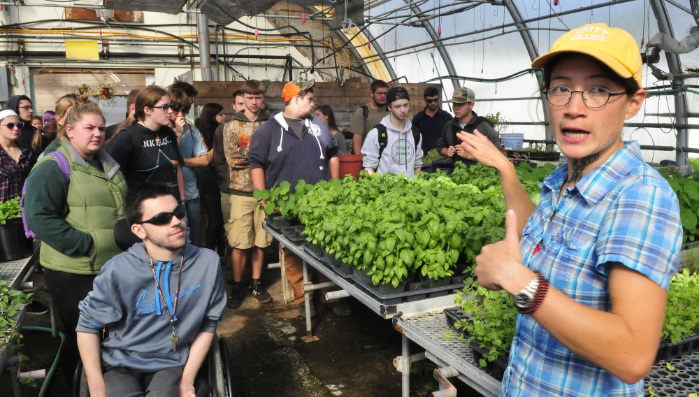 Unity College professor Mary Bulan leads a tour of a greenhouse at the new McKay Farm and Research Station in Thorndike. In the past school year, the center grew 30,000 servings of vegetables for the dining hall.