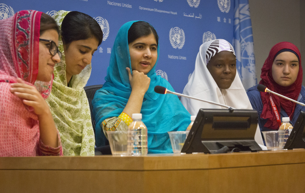 Nobel Peace Prize winner Malala Yousafzai, center, hold a press conference with her friends and youth activists  , Friday Sept. 25, 2015 at United Nations headquarters.  Malala addressed the U.N. General Assembly and urged global leaders to do more to protect and empower young people.  (AP Photo/Bebeto Matthews)