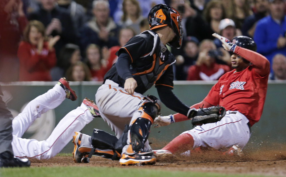 Orioles catcher Caleb Joseph turns as two Red Sox base runners, Dustin Pedroia, left, and Xander Bogaerts, score nearly together on a double by David Ortiz in the sixth inning Friday night.