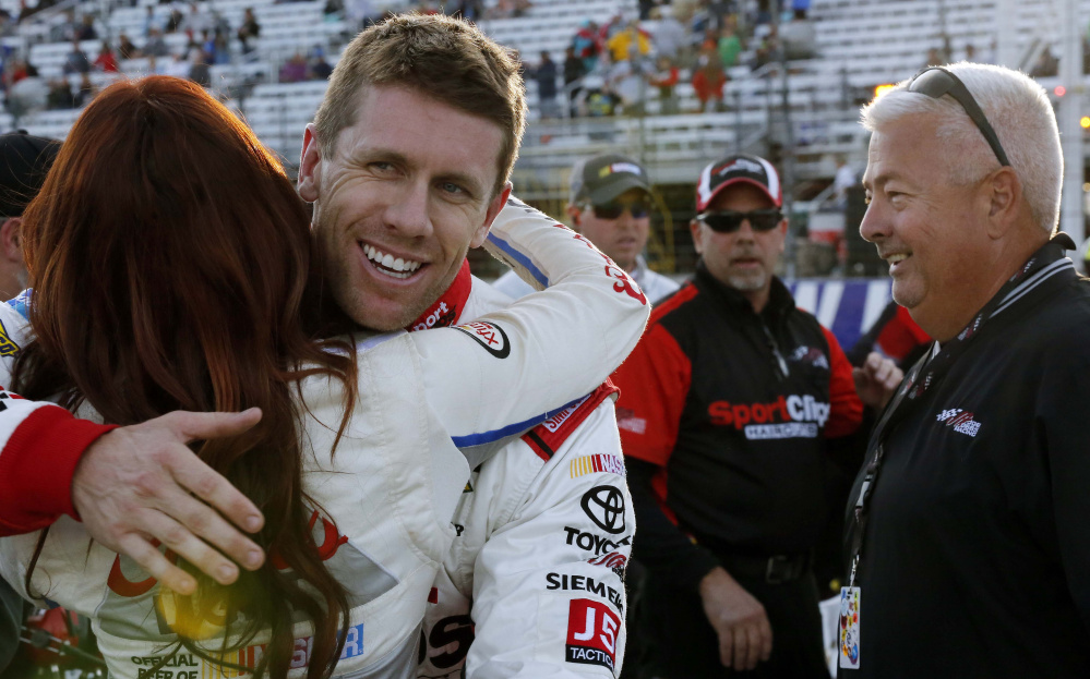 Carl Edwards gets a hug Friday after winning the pole position for Sunday's NASCAR Sprint Cup at New Hampshire Motor Speedway in Loudon, N.H. Edwards also won the pole for the Sprint Cup racing in New Hampshire in July.