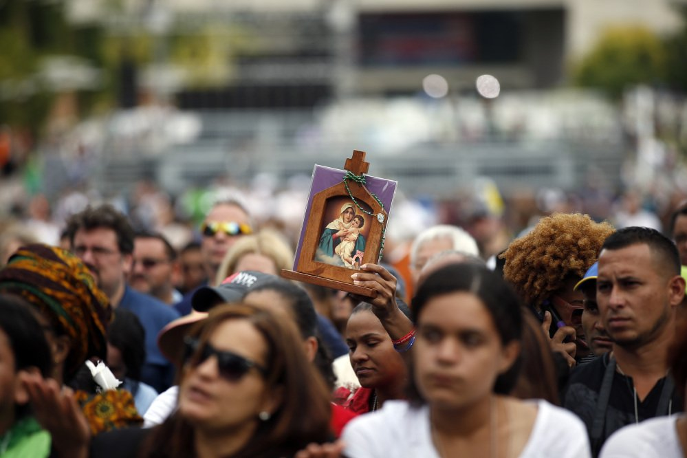 A woman holds an icon while she watches Pope Francis celebrate Mass on a large video monitor as people await the arrival of the pope at Independence Hall on Saturday in Philadelphia.