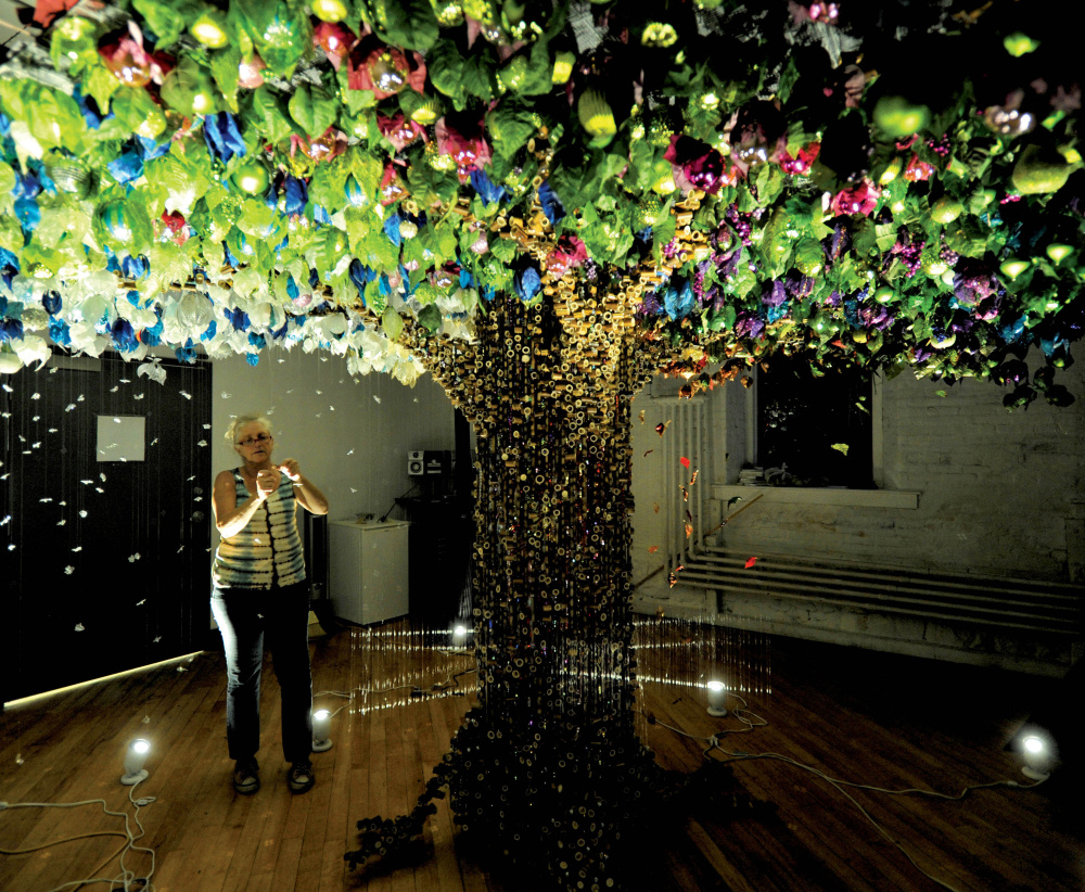 """Robin Protz puts finishing touches on """"Seasons,"""" a 144-square-foot """"holographic sculpture"""" she is entering in the ArtPrize Seven competition in Grand Rapids, Mich. Protz began making art after re-evaluating her life after the 9/11 terror attacks."""