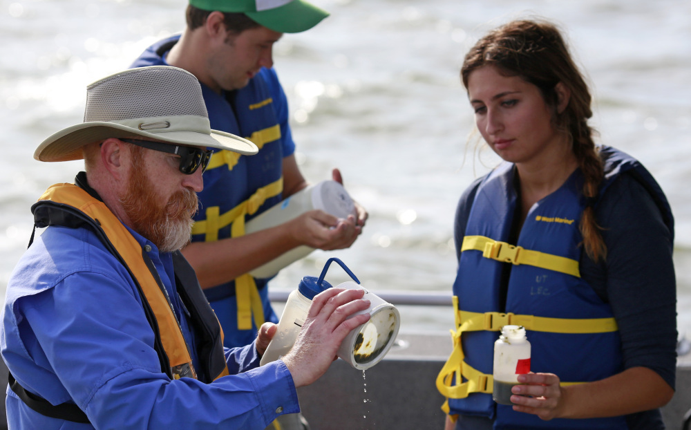 In this Tuesday, Sept. 15, 2015 photo, Thomas Bridgeman, an associate professor in the Department of Environmental Sciences at the University of Toledo, left, along with graduate students Kristen Hebebrand and Ken Gibbons, gather water samples from Lake Erie near the City of Toledo water intake crib, approximately 2.5 miles off the shore of Curtice, Ohio. In the wake of Toledo's water crisis, Ohio has put limits on when and where farmers can spread fertilizer and manure on fields. (AP Photo/Haraz N. Ghanbari)