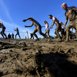 Participants in the Great Northeast Tough Mudder obstacle race climb a muddy hill in Westbrook on Saturday. Organizers of local not-for-profit races that raise funds for charities say the incursion of such for-profit events into Maine is siphoning off their runners.