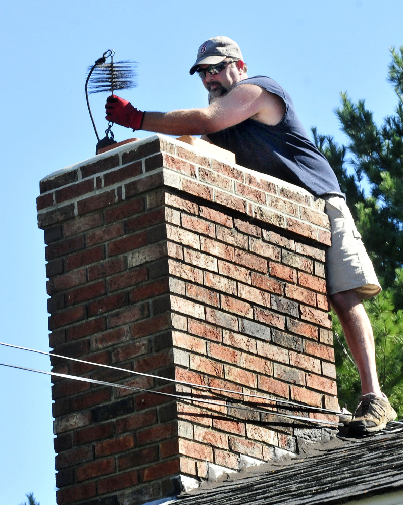 John Beane, of Complete Property Care Management Services, lifts a weighted chimney brush to clean a homeowner's chimney.
