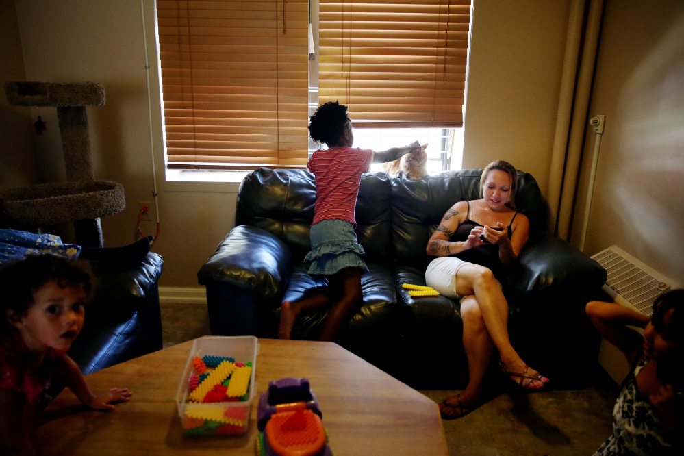 ADVANCED FOR RELEASE SATURDAY, SEPTEMBER 26, 2015 Maria Santos, right, relaxes in her apartment with her children and friends, including Kathryn Tinsley, 8, at the Bunker Hill Development where she lives with her mother Maria Santos in Charlestown, Mass. on Aug. 27, 2015. The Boston Housing Authority planning to redevelop the 1,100-unit housing complex. (Craig F. Walker / The Boston Globe via AP) NO SALES, MAGS OUT, INTERNET OUT, ARCHIVE OUT, BOSTON HERALD OUT, QUINCY OUT