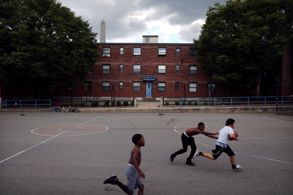 From left, Jewelz Riley and his brother David play football with Evan Yang at the Bunker Hill Development in Charlestown, Mass. Boston will allow development firms to build market-rate apartments if they are willing to build new homes for Bunker Hill's 2,600 residents.