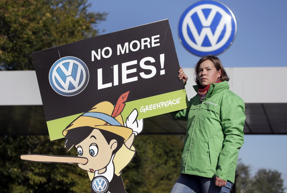 A Greenpeace activist holds a protest poster Friday in front of the Volkswagen factory gate in Wolfsburg, Germany, where the supervisory board met to discuss who to name as CEO after Martin Winterkorn quit the job last week.
