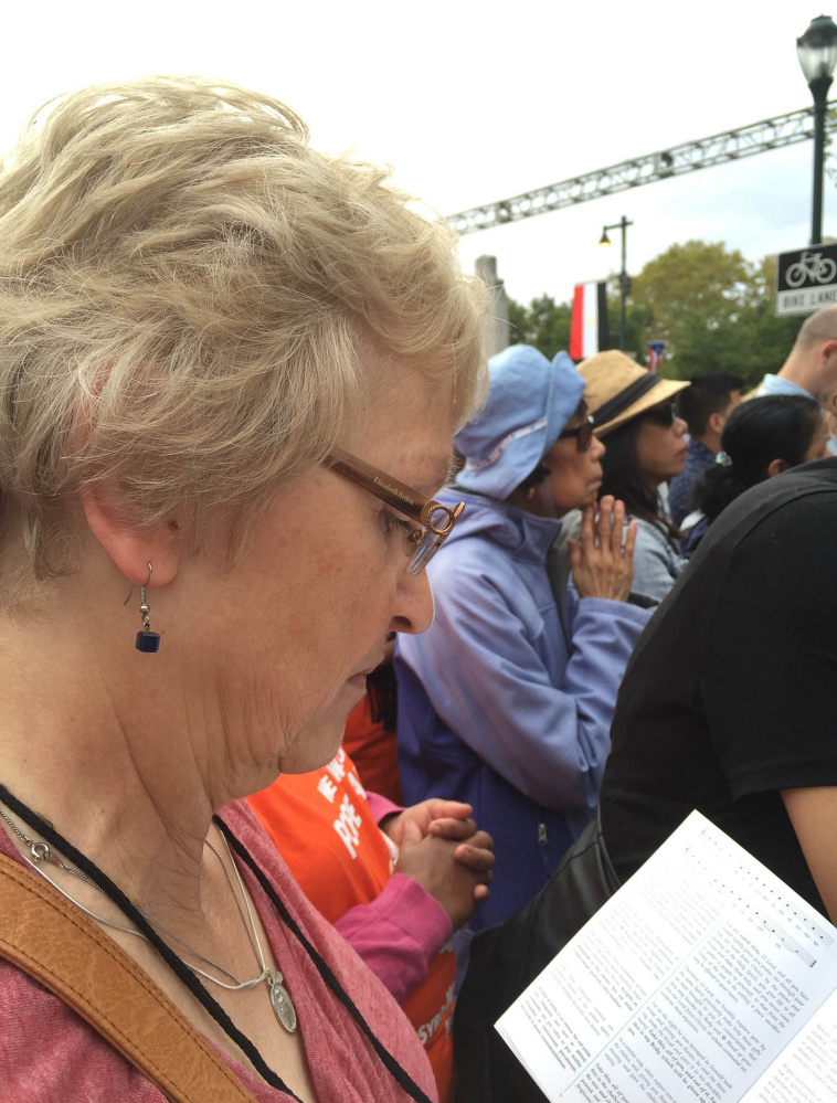 Kay Saucier of Levant, on a pilgrimage organized  by the Roman Catholic Diocese of Portland, reads a translation of a Latin prayer during the Mass that Pope Francis celebrated in Philadelphia on Sunday.