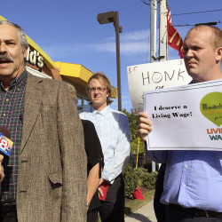 Harlan Baker of the Southern Maine Labor Council, left, speaks at a news conference held outside McDonald's restaurant in Portland Monday to promote a proposed $15 per hour citywide minimum wage that goes to city voters Nov. 3. At right is Tom MacMillan, chair of the Portland Green Independent Committee and candidate for mayor. Photo by Randy Billings/Staff Writer