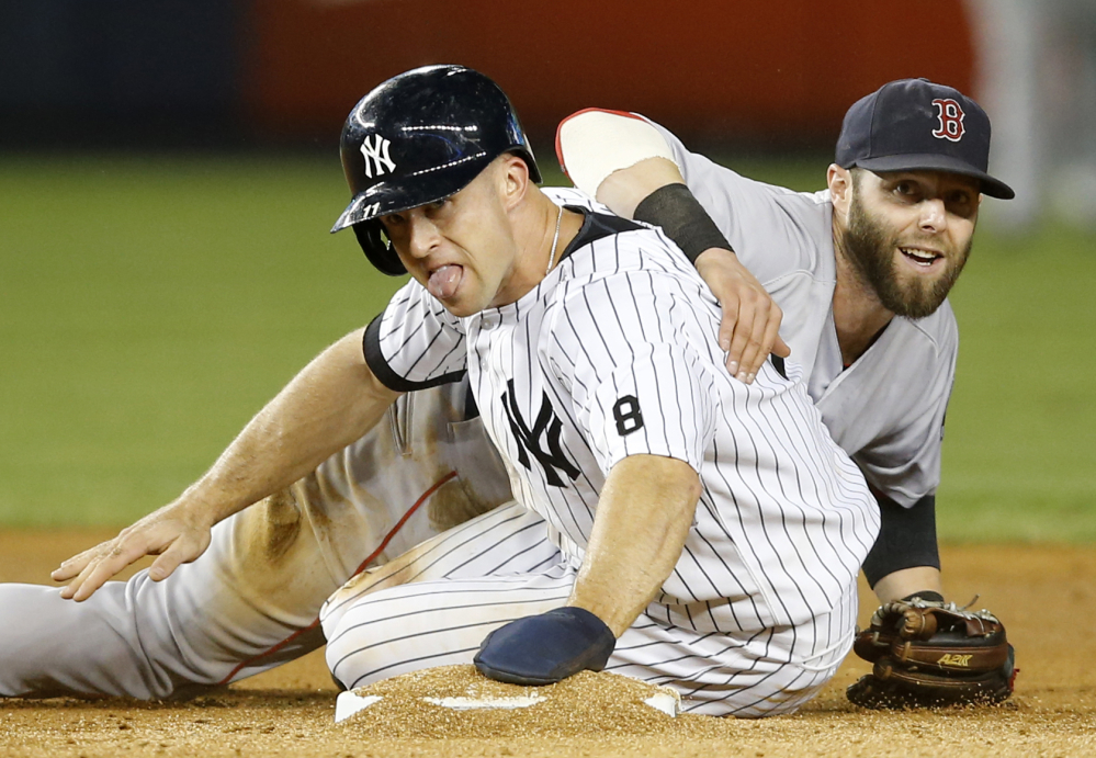 Dustin Pedroia looks from behind the Yankees' Brett Gardner after forcing Gardner out in the fifth inning when Alex Rodriguez hit into double play.