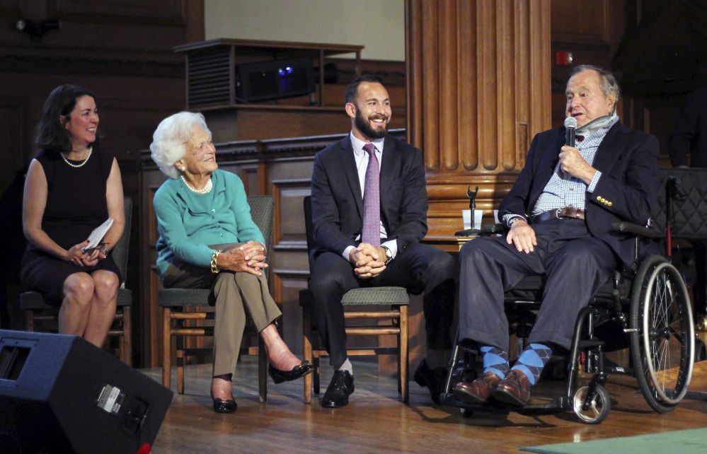 Former President George H.W. Bush, right, speaks Wednesday during a visit to Phillips Academy in Andover, Mass., for a screening of a documentary about the former president. On stage with Bush are Mary Kate Cary, left, executive producer of the documentary, former first lady Barbara Bush and Evan Sisley, an aide to President Bush. Bush, 91, is an alumnus of the class of 1942 at the academy.