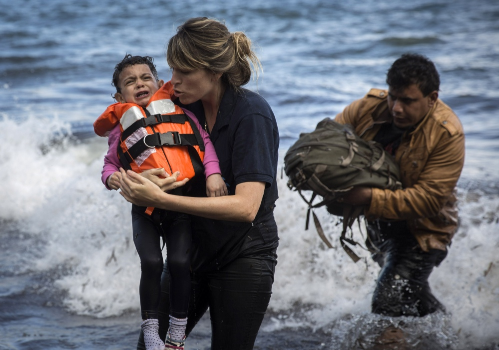 A volunteer holds a Syrian child after arriving with a group of migrants on a dinghy from the Turkish coast to the Greek island of Lesbos on Wednesday.
