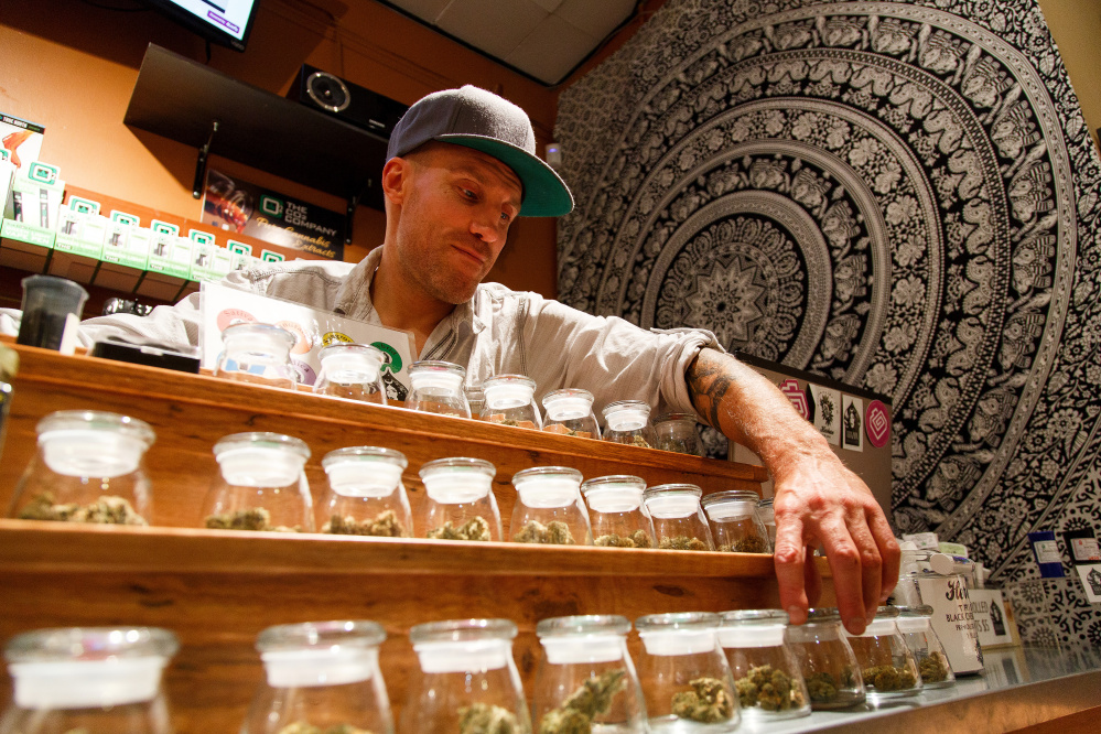 Shane Cavanaugh, owner of Amazon Organics, a pot dispensary in Eugene, Ore., arranges the cannabis display  in his store. The Associated Press