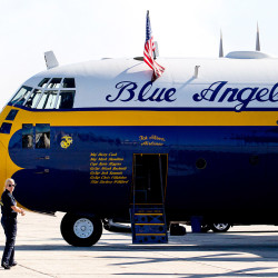 "Katy MacDonald, a public affairs officer with the Blue Angels, makes her way to ""Fat Albert,"" an 80,000-pound C-130T that is part of the Blue Angels crew."