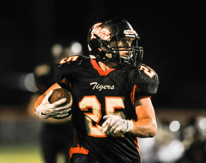 Biddeford fullback Lucas Rhoy checks behind him as he runs past Westbrook defenders in Friday night's game. Rhoy scored touchdowns on runs of 8, 17 and 17 yards.