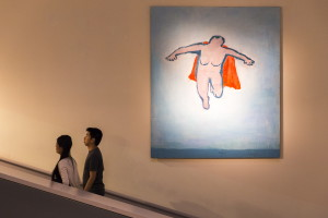 "Chicagoans Angel Wuang and Chris Lam walk past ""Woman Flying,"" a painting by Katherine Bradford, as they acsend from the lower level of the Portland Museum of Art. The museum's ""Directors' Cut,"" a collaborative summer exhibition of works from institutions across the state, continues through Sept. 20. Ben McCanna/Staff Photographer"