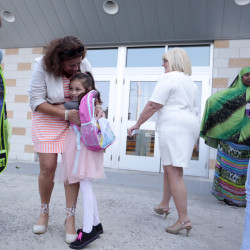 Dorothy Thompson, an Ed Tech specializing in literacy, receives a hug from Stephanie Dwelley, 6, on the first day of school at East End School. Gabe Souza/Staff Photographer