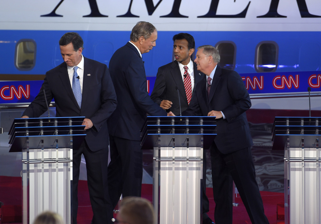 Republican presidential candidates Rick Santorum, left, George Pataki, second from left, Bobby Jindal, second from right, and Lindsey Graham talk at the finish of their debate Wednesday night. The Associated Press