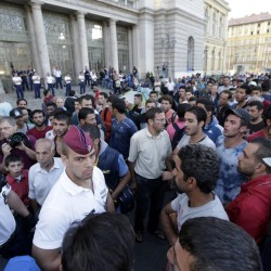 Hungarian policemen talk to some of hundreds of migrants waiting near the Keleti Railway Station in Budapest Wednesday after police stopped them from getting on trains to Germany. Over 150,000 migrants have reached Hungary this year, most coming through the southern border with Serbia. Many apply for asylum but quickly try to leave for richer EU countries. The Associated Press
