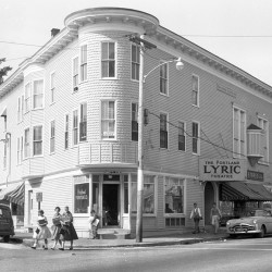 An uncredited staff photograph from September 1960 shows the Portland Lyric Theater building on the corner of Stevens Avenue and Brentwood Street in Portland's Deering Center neighborhood. Today, the corner is the site of Siano's Pizzeria; the building that currently houses Pat's Meat Market is visible in the background near the photograph's right edge.