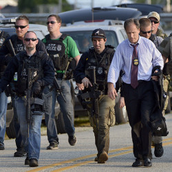 Members of local, state and federal police agencies gather as they continue searching for suspects in the shooting of a police officer Tuesday, Sept. 1, 2015 in Fox Lake, Ill. Fox Lake Police Lt. Charles Joseph Gliniewicz was shot and killed while pursuing a group of suspicious men. Police with helicopters, dogs and armed with rifles are conducting a massive manhunt in northern Illinois for the individuals  believed to be involved in the death of the three-decade member of the department and a father of four sons. (AP Photo/Michael Schmidt)