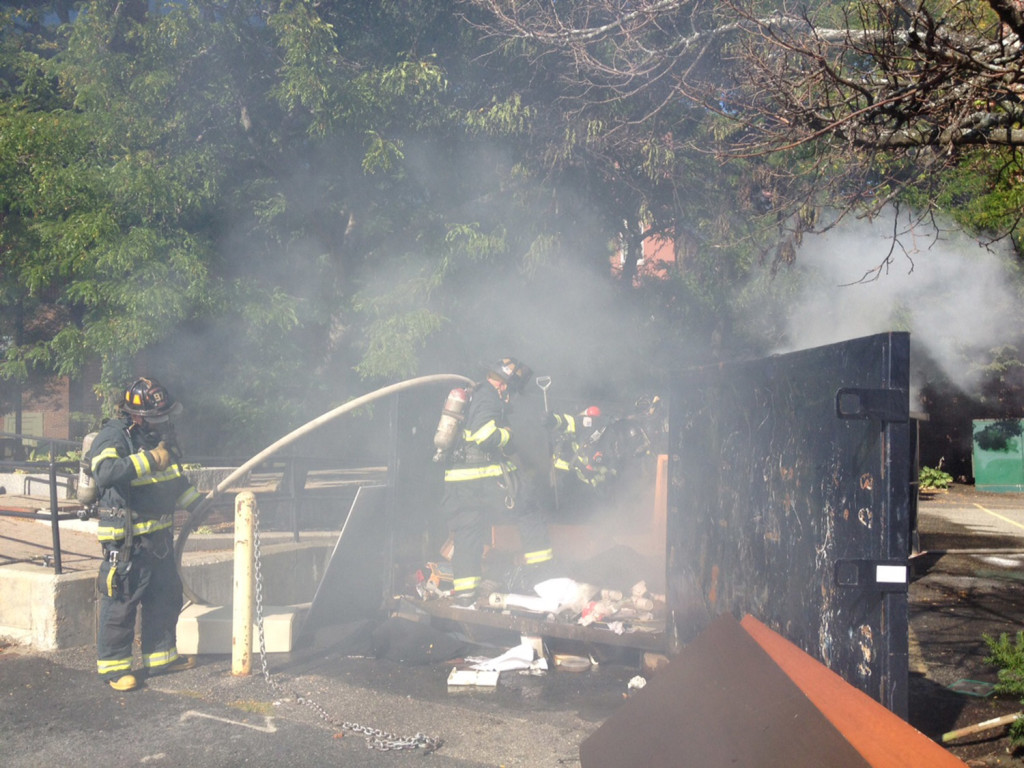 Portland firefighters extinguish a fire in a trash container on Cross Street on Friday afternoon.