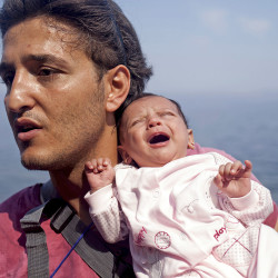 SEPT. 3: A Syrian refugee from Aleppo holds his 1-month-old daughter moments after arriving on a dinghy on the Greek island of Lesbos. Greece will ask the European Union for about 700 million euros to build infrastructure to shelter the hundreds of refugees and migrants arriving on its shores daily, the government said on Thursday. The cash-strapped country has seen a rise in the number of refugees and migrants – mostly from Syria, Iraq and Afghanistan – arriving on rubber dinghies from nearby Turkey.