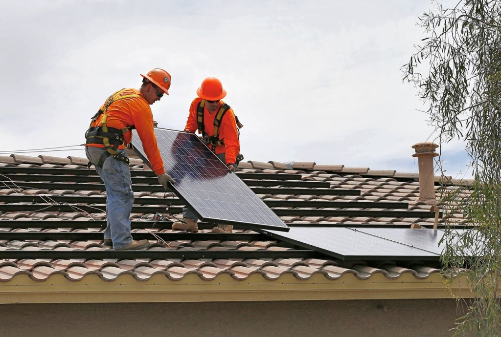 Electricians install solar panels on a roof for Arizona Public Service company in Goodyear, Ariz. Traditional power companies are getting into small-scale solar energy and competing for space. The Associated Press