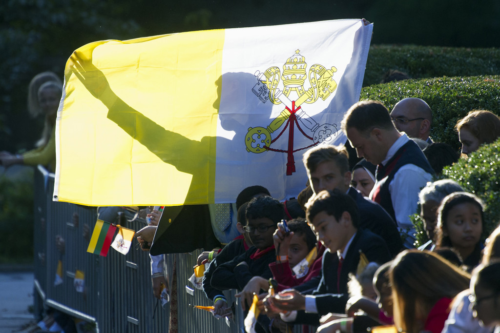 A man holds up a Papal flag as he waits for Pope Francis departure from the Apostolic Nunciature, the Vatican's diplomatic mission in Washington, Wednesday. The Associated Press