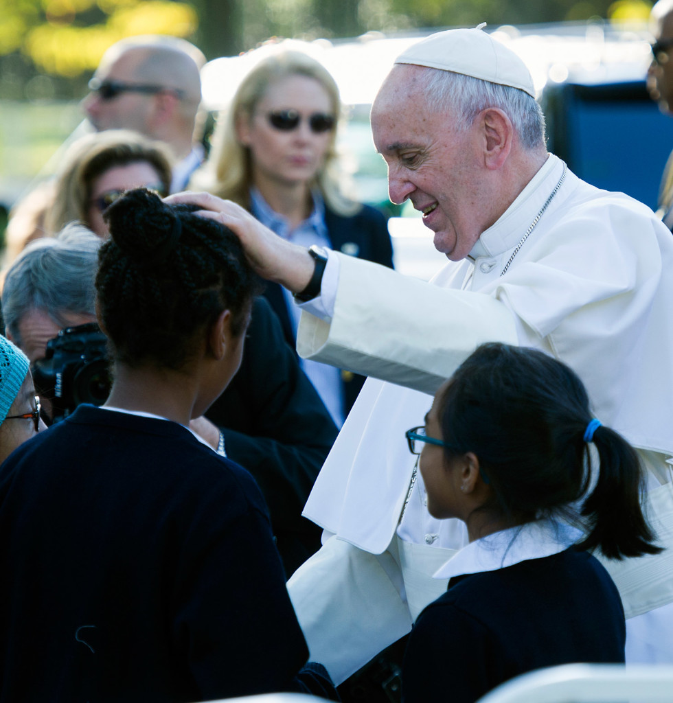 Pope Francis places his hand on the head of a girl as he greets schoolchildren prior to departing the Apostolic Nunciature, the Vatican's diplomatic mission in the heart of Washington, on Wednesday.