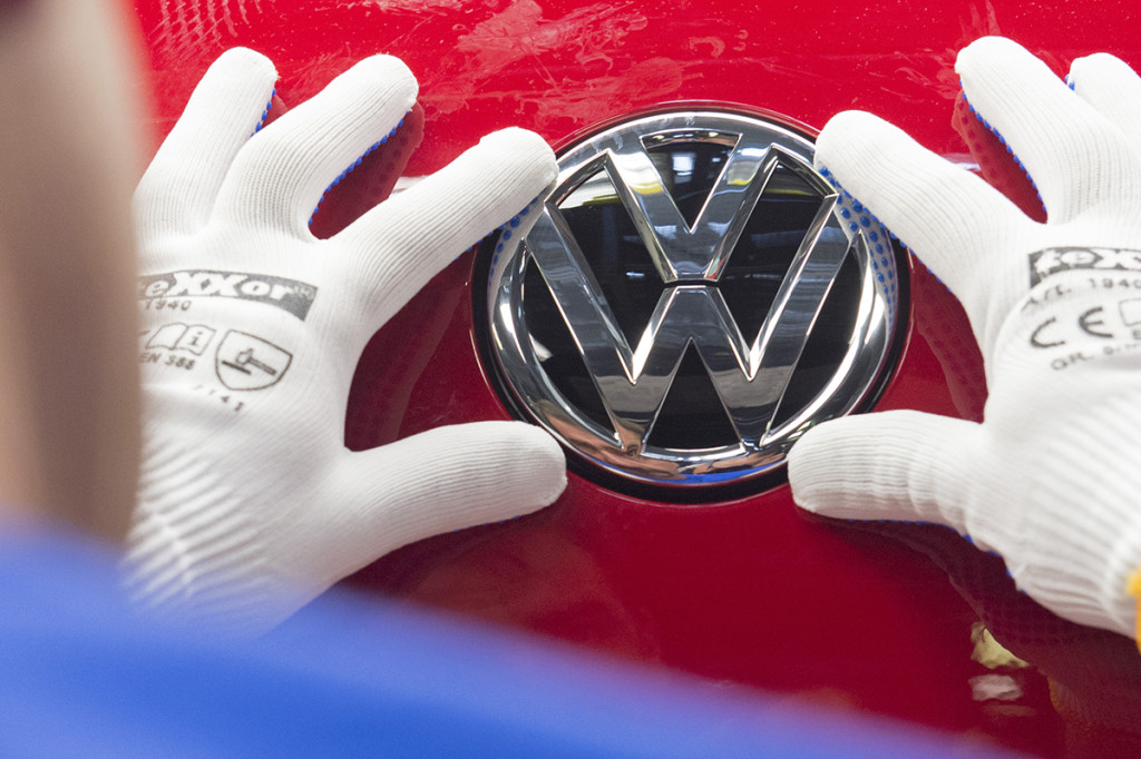 "A worker checks the Volkswagen badge on a Golf car in this In this Sept. 6, 2015, photo. . Above and beyond legal problems, the  company's growing emissions scandal is a huge problem for a brand long identified with trustworthiness and reliability. And there are concerns that could spill over into a wider image problem for goods ""made in Germany."" The Associated Press"