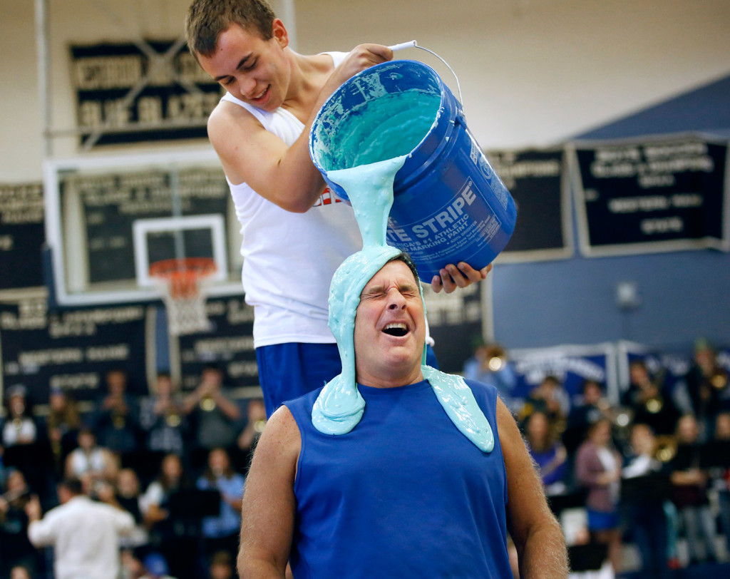 Westbrook High School Principal Jon Ross grimaces as the sliming begins during an annual pep rally at the school Wednesday. Wielding the bucket is senior Josh Miner. As part of fundraiser, money was put in jars corresponding to four schools officials and Ross had the most money in his jar. So he got slimed. (Derek Davis/Staff Photographer)