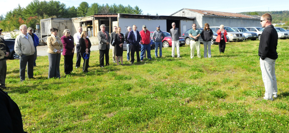 Standing on top of a containment hill filled with waste from the former Wilton Tannery, background, new owner John Black thanks the many supporters and agencies that assisted in the purchase and renovations at the site in Wilton on Thursday.