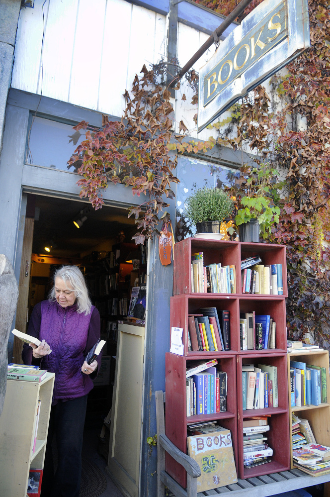Edda Briggs Thiele sorts titles Monday at RiverBooks in Hallowell, which she is closing at the end of the month.  Briggs Thiele has operated the tiny 24-year-old business on the honor system, with clients leaving money behind for books the selected.