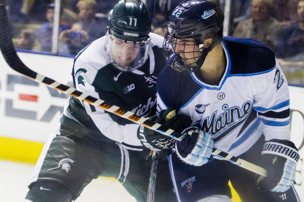 Maine freshman Brendan Robbins fights for the puck with Michigan State's Rhett Holland. Ben McCanna/Staff Photographer