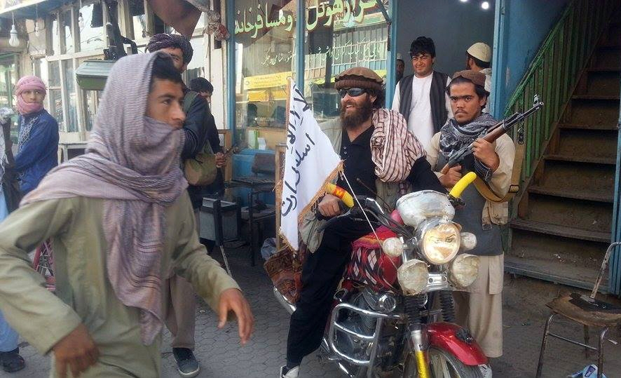 A Taliban fighter sits on his motorcycle adorned with a Taliban flag in Kunduz, Afghanistan, on Tuesday. Afghan troops are preparing to try to drive out the insurgents.