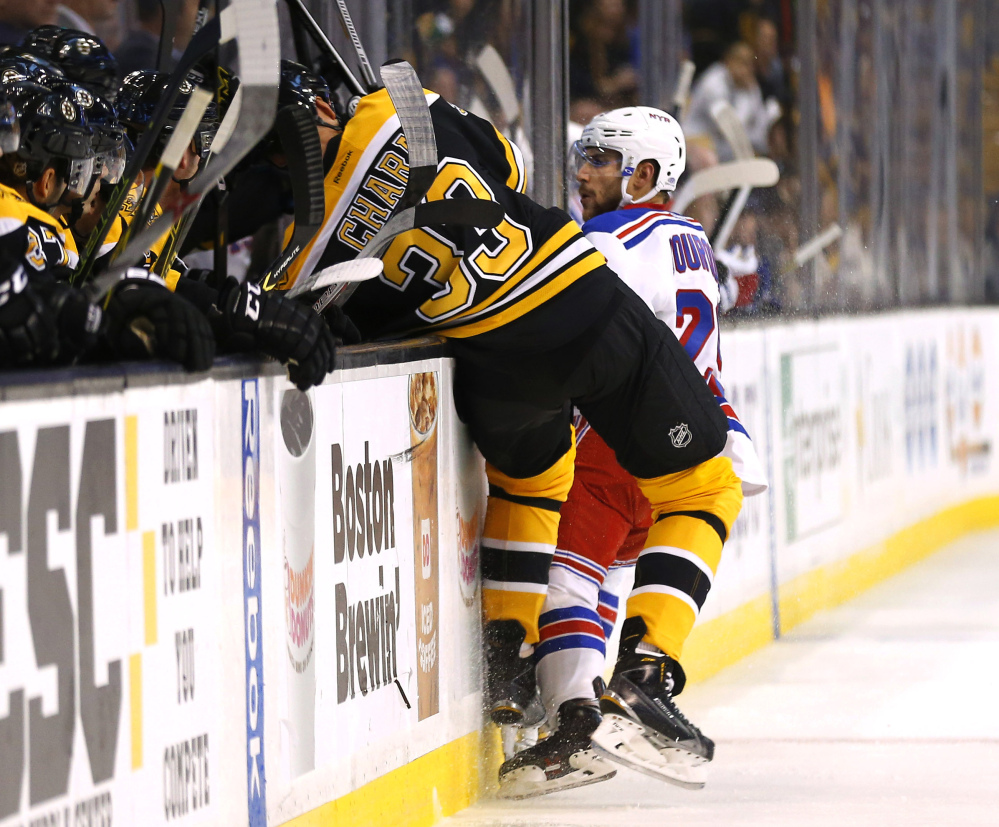 Boston Bruins defenseman Zdeno Chara is checked into the boards by New York Rangers' Ryan Bourque during the first period of a preseason game in Boston on Sept. 24. Chara was injured on the play and left the game. The Bruins hope he will be ready for the regular-season opener Oct. 8.