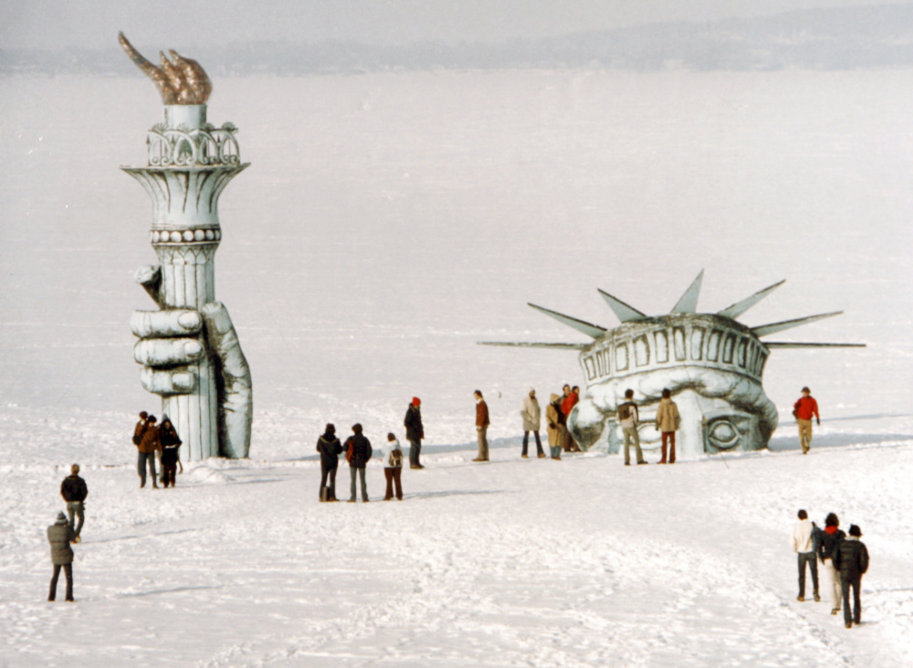 "Madison, Wis., residents surround ""Miss Liberty"" that appears to be poking through the ice of Lake Mendota in 1979. The stunt was the handiwork of the whimsical Pail & Shovel Party, headed by Leon Varjian and Jim Mallon."