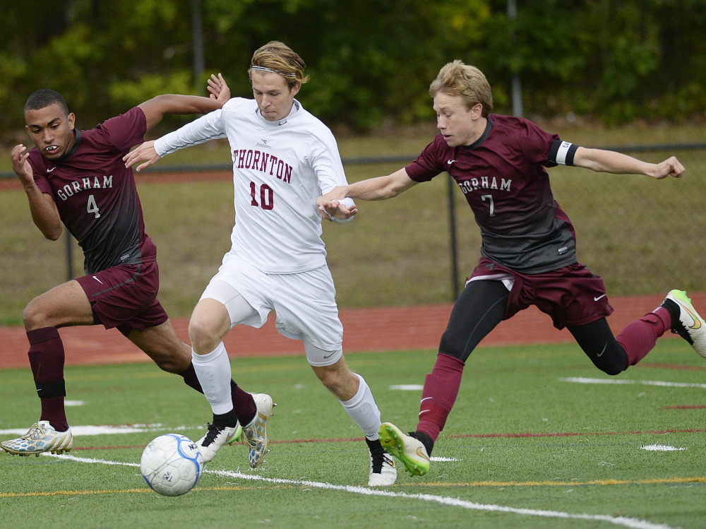 Simon Trcka, who scored three goals for Thornton Academy, looks to break in while defended by Emerson Fox, left, and Jackson Taylor of Gorham. Trcka scored his first goal on the play.