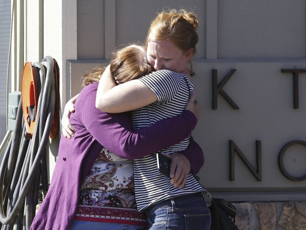 Umpqua Community College alumnus Donice Smith, left, is embraced after she said one of her former teachers was shot dead, near the site of a mass shooting at the college in Roseburg, Oregon, on Thursday.