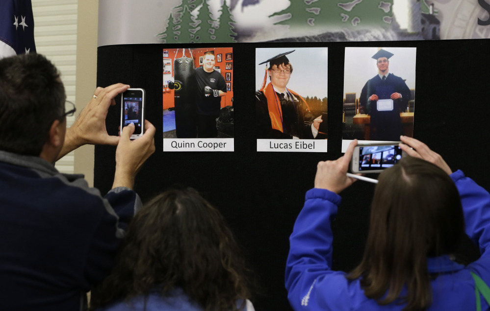 Reporters copy photographs of three of the victims of the mass shooting at Umpqua Community College that were displayed at a news conference Friday in Roseburg, Ore.  In the photos, from left, are Quinn Cooper, 18, Lucas Eibel,18,  and Jason Johnson, 33.
