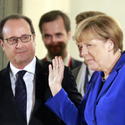 German Chancellor Angela Merkel leaves the Elysee Palace in Paris, France, after a meeting Friday with French President Francois Hollande, left, on the prospects for peace in Ukraine.