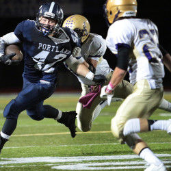 Portland running back George Chaison-Lapine tries to break away from the grasp of Cheverus linebacker Rylan Benedict as Max Coffin comes in to help during the second quarter of Friday's game at Fitzpatrick Stadium. Portland won, 16-14.