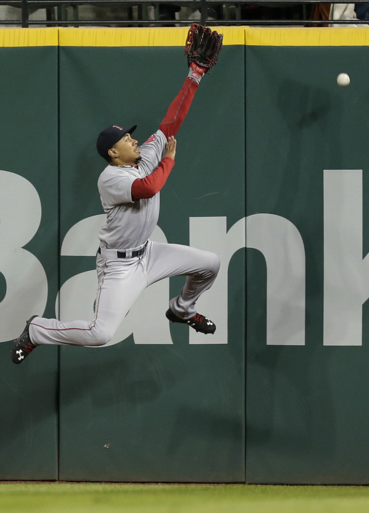 Mookie Betts jumps at the wall but can't reach a ball hit for an RBI double by the Indians' Yan Gomes in the fifth inning of Cleveland's win. Carlos Santana scored on the play.