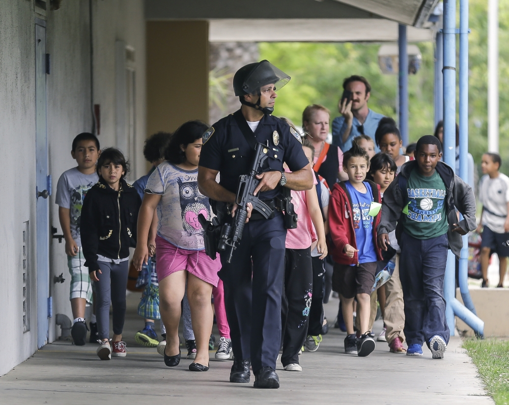 As school shootings continue, scenes such as this one are also more familiar. On June 7, 2013, an armed police officer leads young visitors away from California's Santa Monica College following a shooting in the area. Six people were killed in the incident, including suspected gunman John Zawahri.