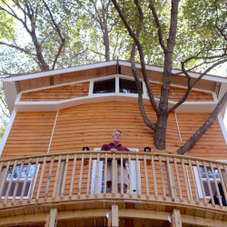Jay Hewitt stands on the deck of a treehouse he built for his grandchildren in his backyard in Attleboro, Mass. The fully enclosed structure, made from salvaged leftovers, features a family room, loft for sleepovers and built-in spiral slide.