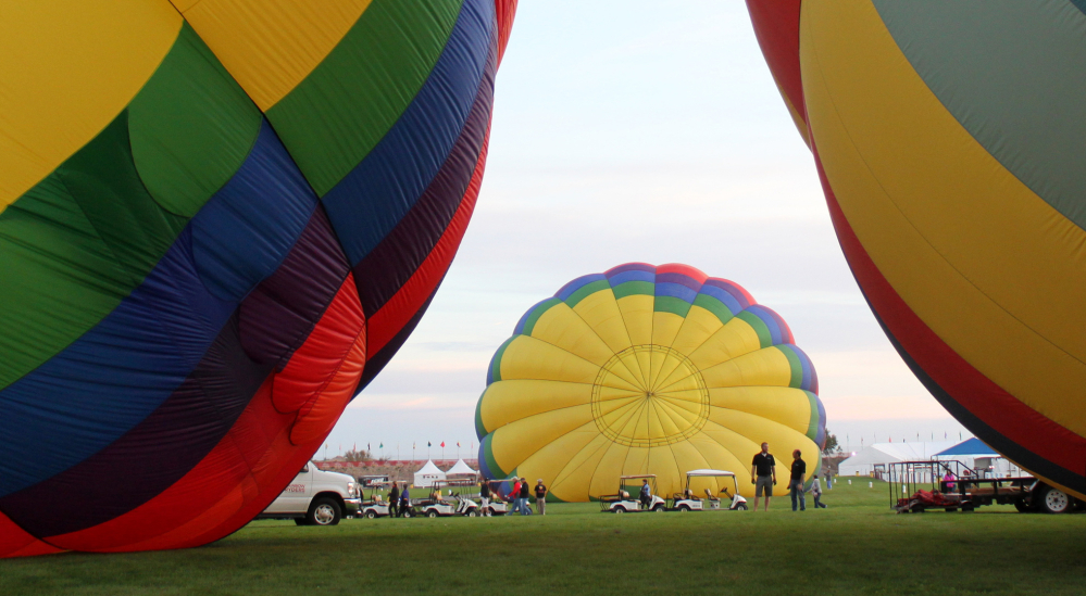 At top, a balloon passes in front of the moon on opening day of the balloon festival in Albuquerque, N.M., on Saturday. Above, left, balloons are inflated on Friday in advance of the nine-day event, which launches with a mass ascension of hundreds of balloons.